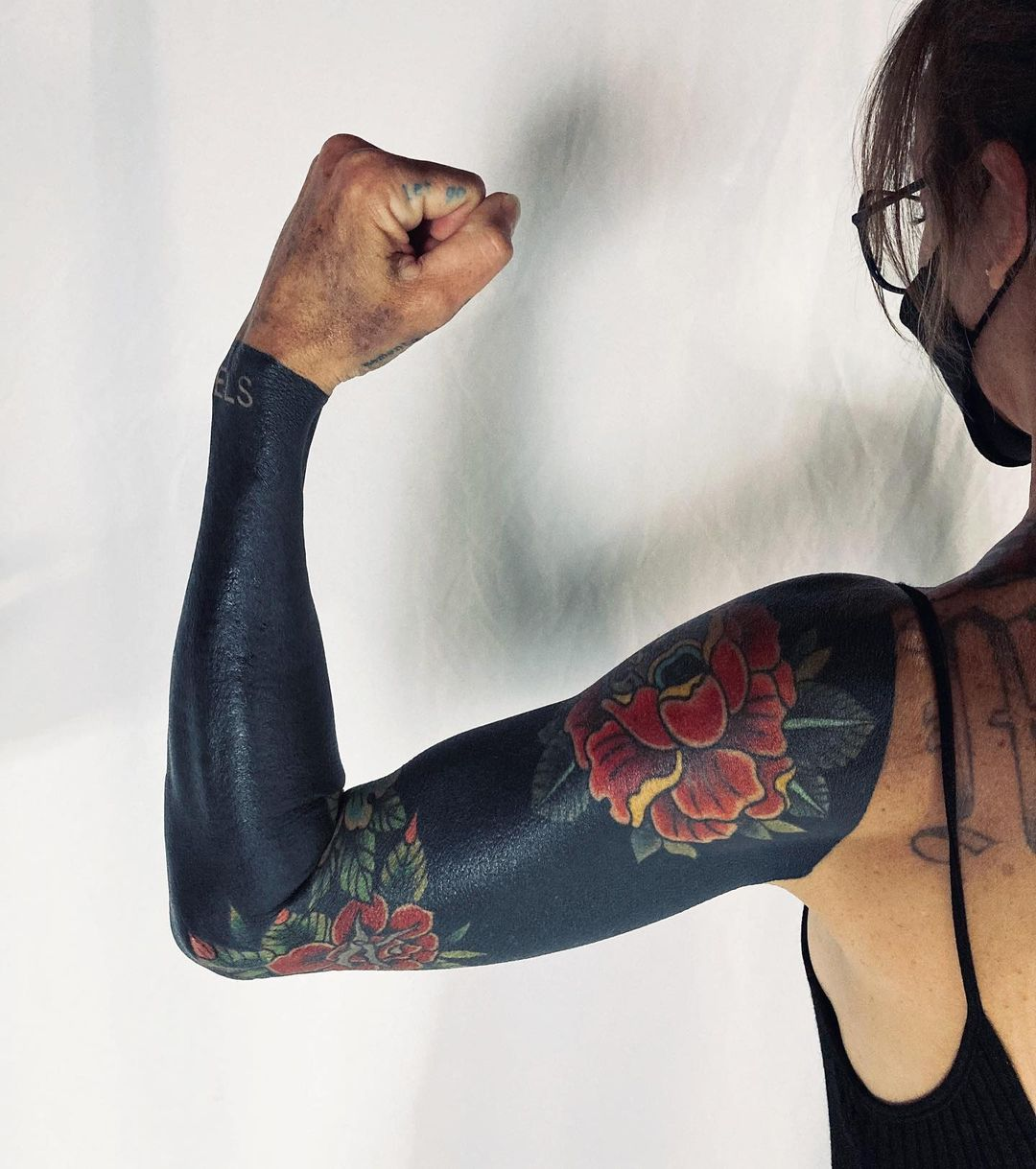 blackout neotraditional flowers tattoo